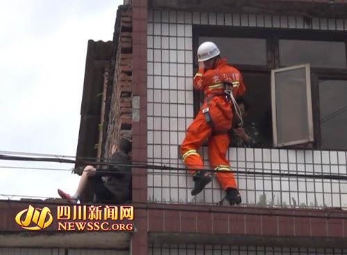 消防战士从阳台上一个箭步跨过去用脚将轻生妇女抵住