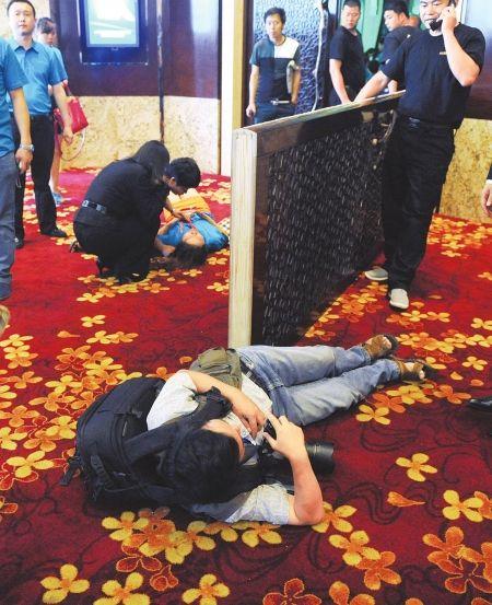 大门突然倒塌,一名摄像师和身穿蓝色衣服的女员工被砸倒。