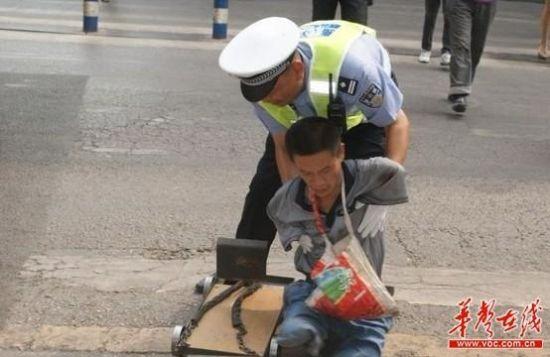 顶着烈日,邓拥军在绿灯亮起时,推着四肢残疾的乞讨者过马路。网友供图