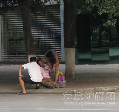 小伙子女友在热心市民的帮助下,对其进行急救。