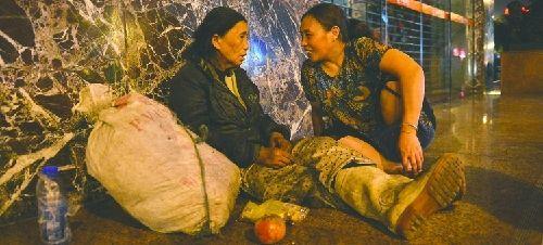 叶昌贵的妹妹叶昌卫(右)询问流浪太婆的情况