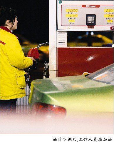 油价下调后,工作人员在加油
