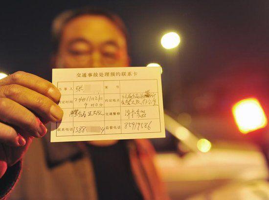 11月21日晚,交警给车主填写好一张事故处理预约卡。
