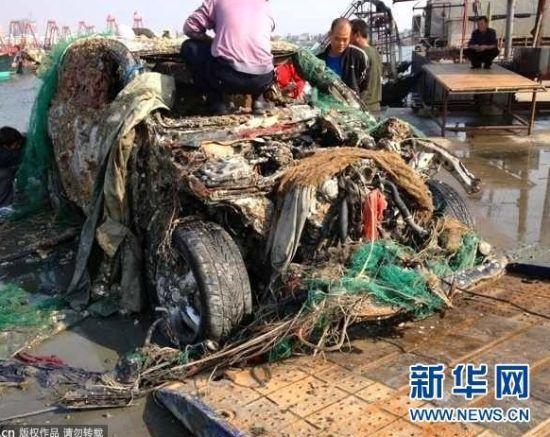 """2012年12月9日上午,广西北海,地角外贸码头,一渔民从海上拖上来一辆保时捷""""卡宴""""豪华越野车,引起了众多市民前来观看"""