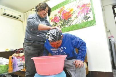 """12月19日,熊丽君在家为儿子洗头,要带他去剪个""""帅气的发型""""。"""