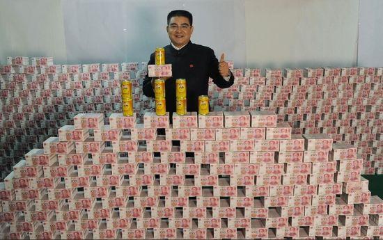 陈光标站在钱山前宣传自己的茶饮料。新浪微博供图