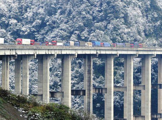 雅西高速因大雪实行交通管制,腊八斤大桥排列的车辆缓行。