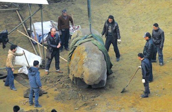 """1月8日,考古工作人员指挥吊车将石兽吊起""""站""""稳。"""