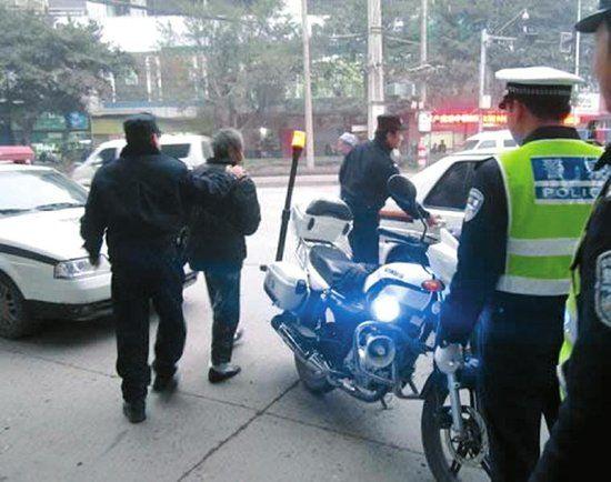 警方将持刀男子(左二)带走。