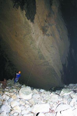 探险队员通过绳索降落到洞穴底部的乱石斜坡上