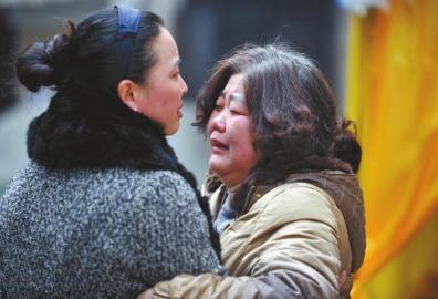 2月6日,朋友安慰春磊的妈妈熊丽君(右)。 张磊摄