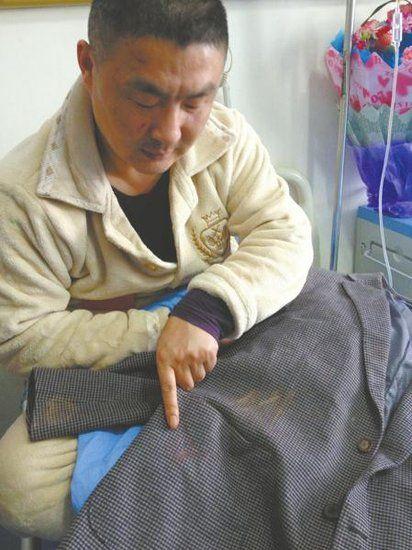 侯某指着被打时所穿衣服上的血迹。