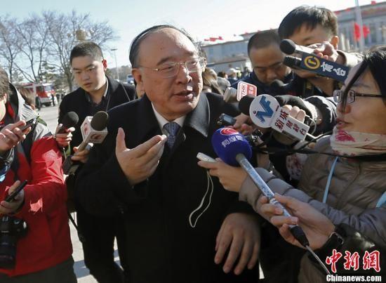 3月4日上午,十二届全国人大一次会议预备会议在北京人民大会堂举行。全国人大代表、重庆市市长黄奇帆进入会场前回答记者提问,他表示欢迎记者到重庆来看看。中新社发张浩 摄