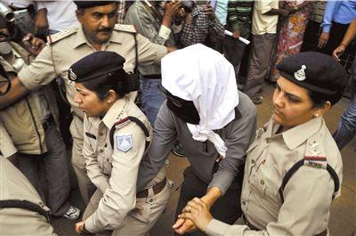 16日,印度中央邦瓜廖尔,警察护送受害瑞士女子到医院接受检查。图/CFP