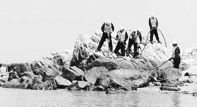 原文配图:炸礁队官兵正在裸露的礁盘上灌注炸药。 刘方泉摄
