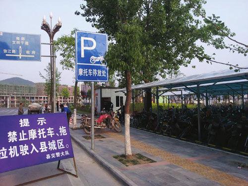 """城区入城口的""""禁摩""""标识和摩托车停放点"""