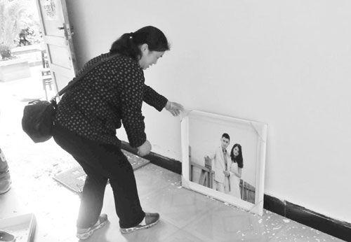 4月22日,双石镇双河村,余有芳正在拾起儿子媳妇的婚纱照