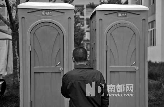 灾区厕所紧张,一灾民在临时厕所外等待如厕。东方IC