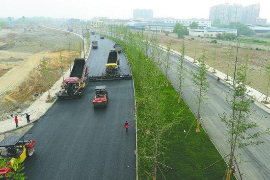 通车在即,金芙蓉大道昨仍在紧张地铺沥青