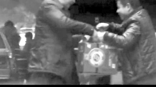 """视频记录""""风衣男""""正接受礼品。(视频截图)"""