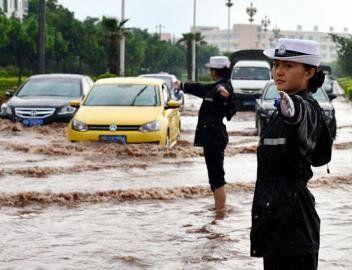 西昌女子交警中队民警在暴雨中执勤。