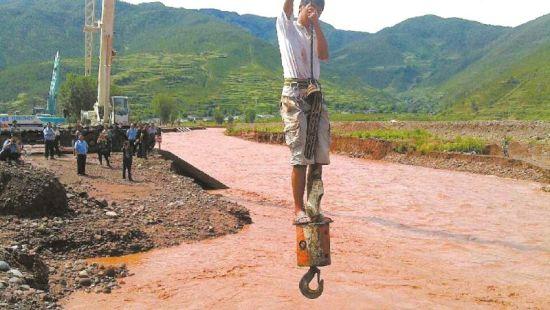 被困人员站在吊车挂钩上脱险。