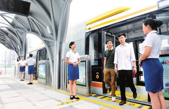 成都二环路快速公交乘务人员引导乘客上下车。张磊摄