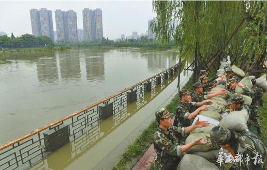 6月20日上午,华阳锦江河段正北下街,武警官兵用沙袋筑成一道防洪堤。