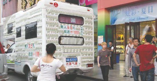 这辆贴满人民币的房车在某百货公司门口一亮相,就引来市民围观