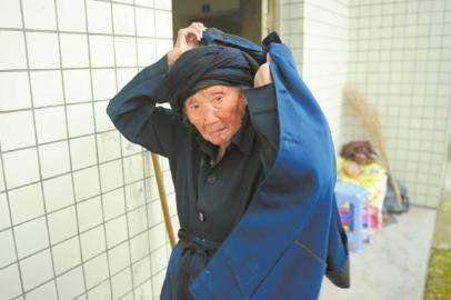 付素清老人加减衣服,动作利落。