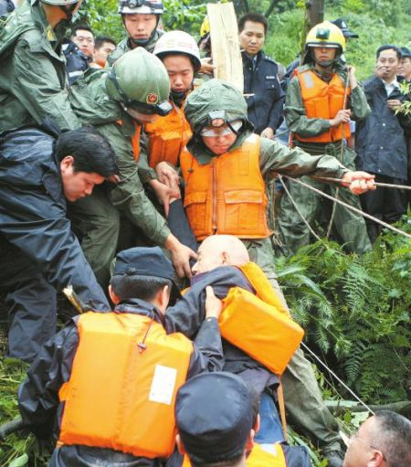 7月11日,彭州龙门山镇回龙沟小区,救援人员救出被困的老人。