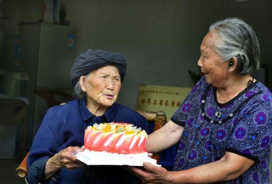 7月19日,付素清老人满116岁,女儿为母亲端上生日蛋糕。