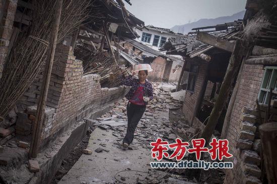 4月21日,四川省雅安市芦山县龙门乡,一村民举着脸盆作为保护,端着一碗饭快速通过因地震而松动的墙体。杨深来 早报资料