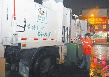 环卫工人蒋刚正往餐厨垃圾收运车上运送垃圾。