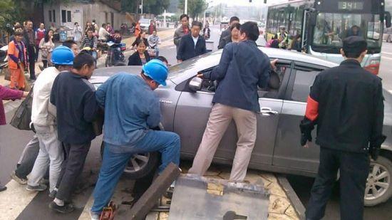 9月9日上午,成都双庆路口众人帮忙抬车