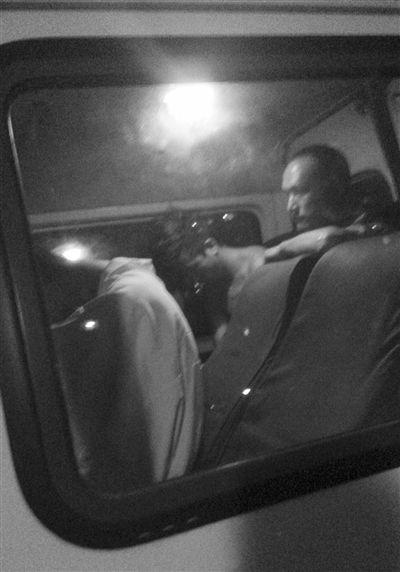 一男子赤裸上身(圈内)被警方带走。读者供图