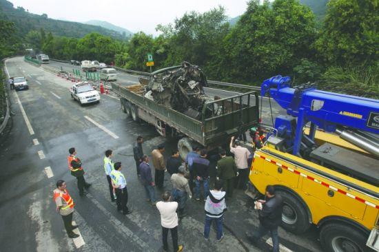 昨日,成渝高速车祸现场,救援人员清理最后一辆事故车
