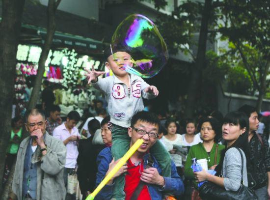 10月2日,成都宽窄巷子游客爆满。一位小朋友在玩泡泡