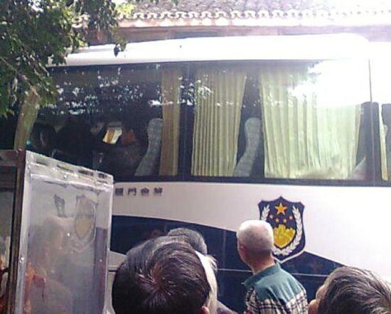 相关人员陆续被带上车(车下为围观市民)。(网友供图)