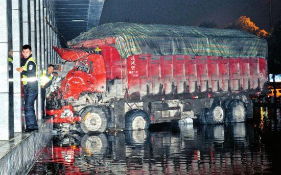 10月29日凌晨,一辆大货车连续撞倒大树、路灯后,一头撞上了路旁的一幢大厦。