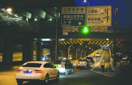 """二环路高架万达广场匝道口,图中绿色箭头亮起,车辆通行;当绿色箭头变成""""红叉""""时,车辆禁入 摄影记者 王效"""
