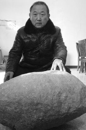"""杨正玉向记者展示他收藏的""""怪石"""