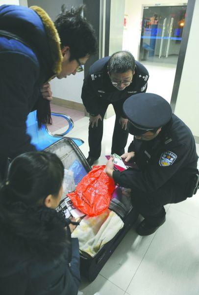1月18日晚,民警余斌打开行李箱寻找主人线索