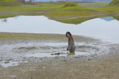 女子在泥潭中等待救援。