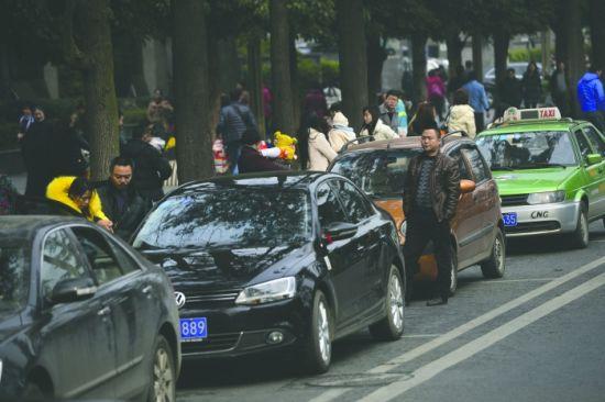 """昨日,人民南路,多辆轿车在""""即停即走""""路段的路边停靠,一名驾驶者站在车旁 摄影记者 程启凌"""