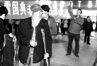 """在漯河高铁西站,志愿者打出""""欢迎老兵雷国典回归家乡""""的横幅。"""