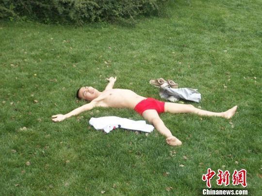 """绝症大学生裸体""""摆大字""""躺在草坪上。王海江 摄"""