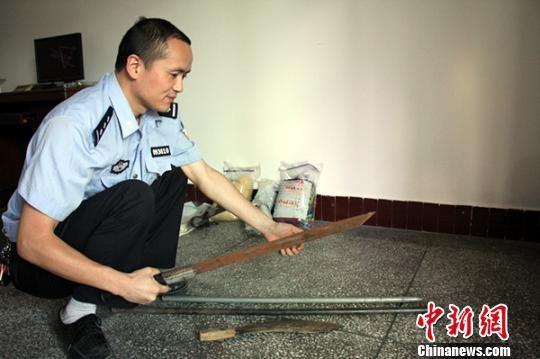 办案民警展示绑架轮奸作案威胁受害人和与民警对抗的刀、钢管
