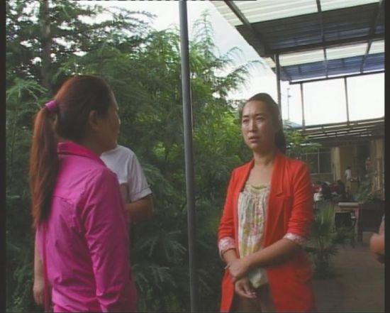事发当天,调查人员正在与谢梅(左)交谈。(图由盐源县纪委提供)