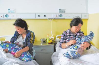 8月5日,在鲁甸县人民医院,常臣淑(右)和李世琼抱着刚出生不久的孩子。新华社发